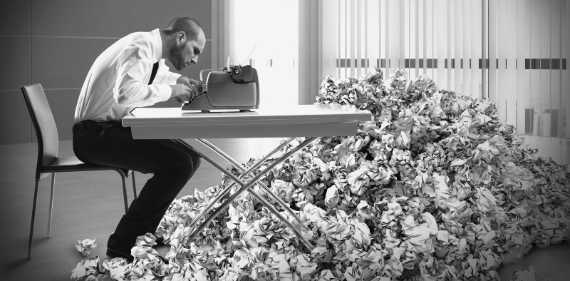 Overworked exhausted businessman writes with a typewriter